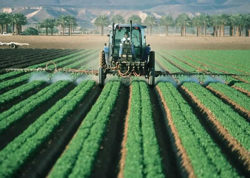 Farm tractor spraying pesticide.