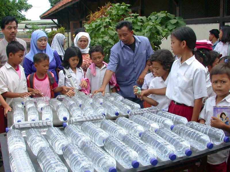 In a community in Indonesia, a group of people in a yard are gathered around two tables, where about four dozen clear, plastic bottles of water lay on their sides.