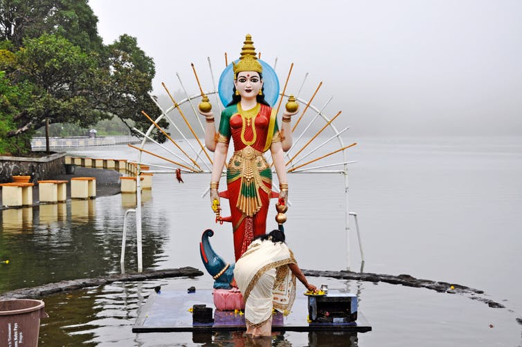 Lady giving offerings to a Hindu God.