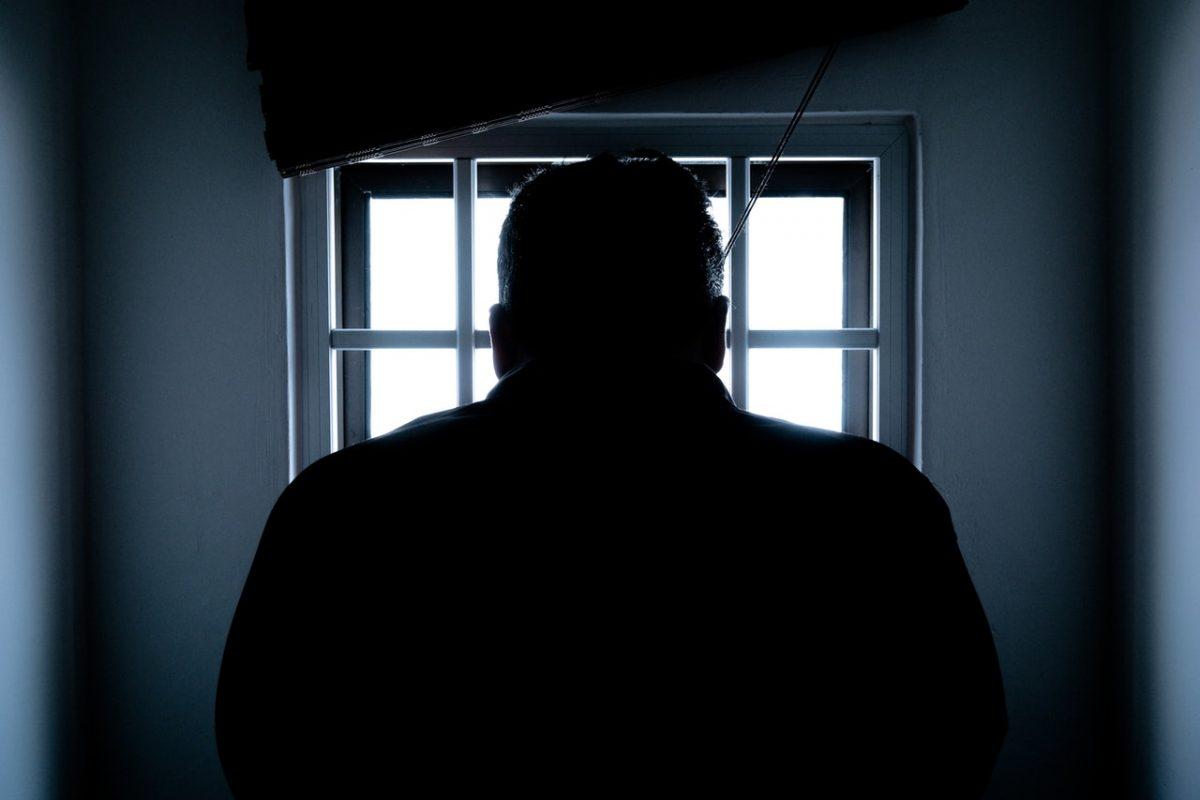 Silhouette Of A Man In Window giving death penalty last rites.
