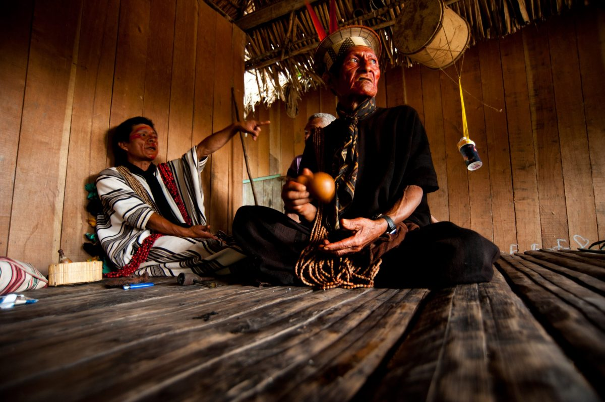 Two Ashaninka (Amazonian peoples) men sitting on a wooden floor