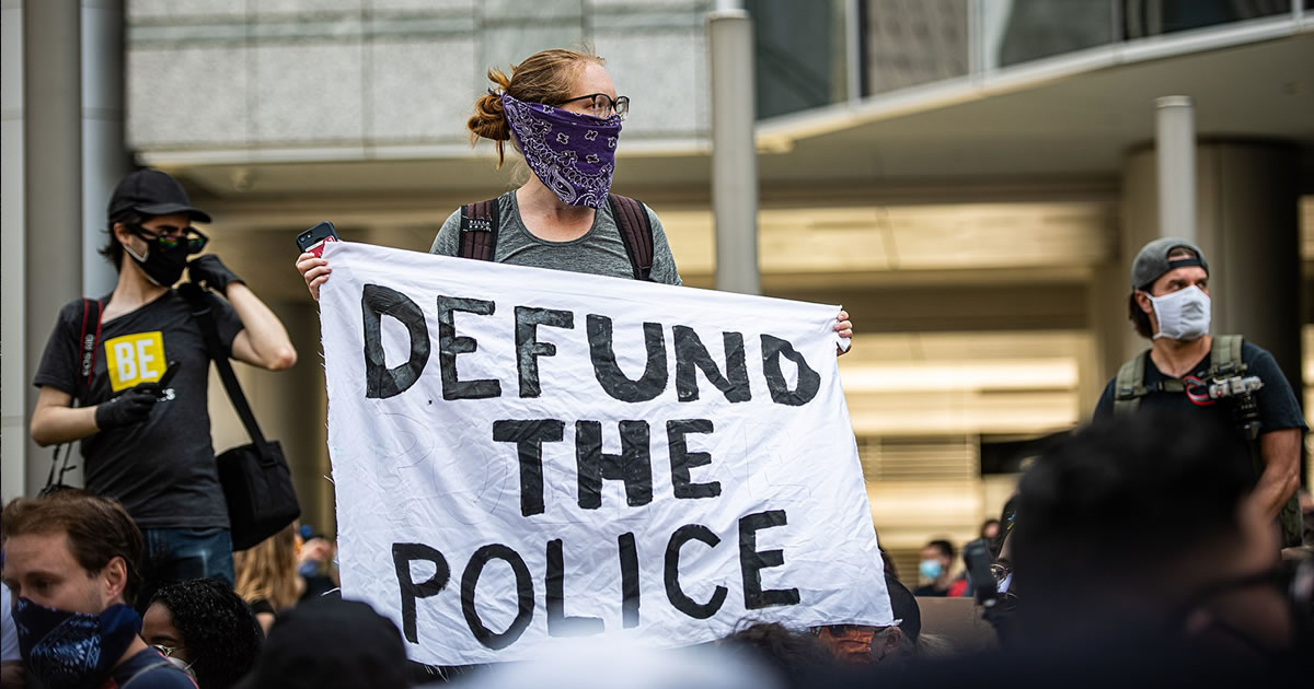 "Lady protester amidst a crowd holding up a sign stating ""Defund the Police""."