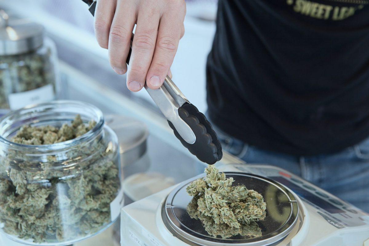 A man adding weed to a scale at a marijuana dispensary.